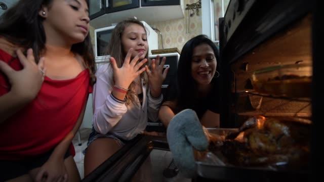 vídeos de stock e filmes b-roll de family checking the traditional turkey for christmas dinner - three people
