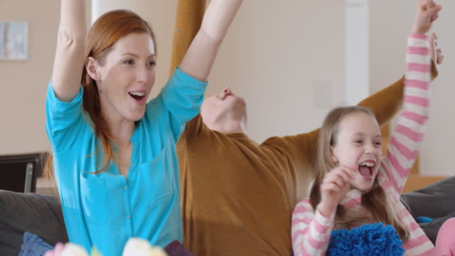 family cheering and celebrating in front of tv - in front of stock videos and b-roll footage