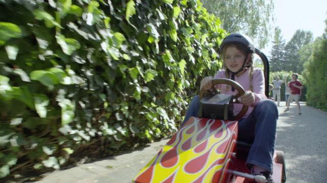 MS POV Family cheering girl (8-9) driving toy car on path, Encino, California, USA