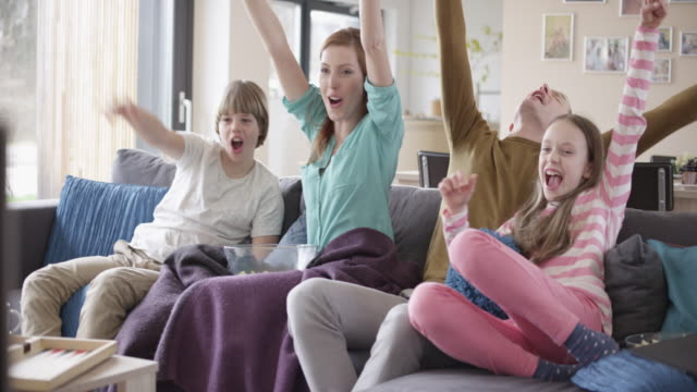 Family cheering in front of TV