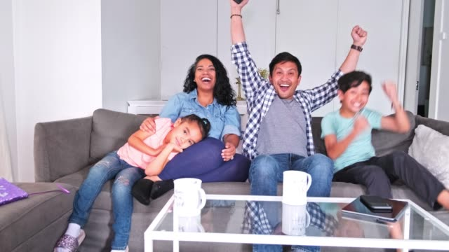 family cheering while watching tv at home - teenage girl watching tv stock videos & royalty-free footage