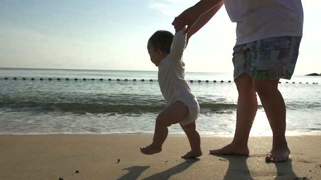 family, child, childhood and parenthood concept - happy little baby learning to walk with mother help at home - primi passi video stock e b–roll
