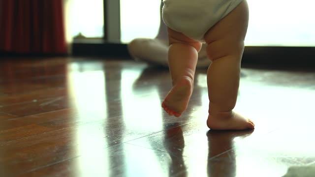 vídeos de stock, filmes e b-roll de família, criança, infância e conceito de paternidade - feliz bebê aprendendo a andar com o pai em casa com seu pai animar como primeiro plano. - bebês meninas