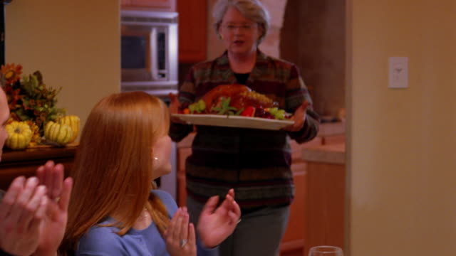 A family claps as a mother brings the Thanksgiving turkey to the table.