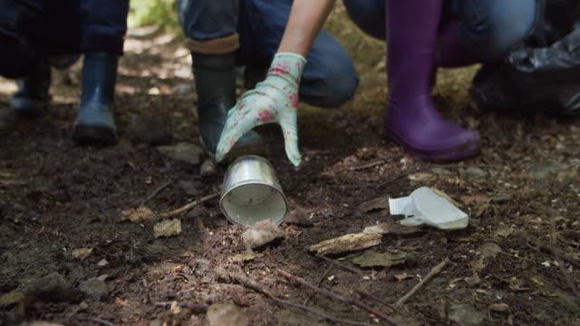 vídeos de stock e filmes b-roll de family cleaning trash in the forest - apanhar atividade física