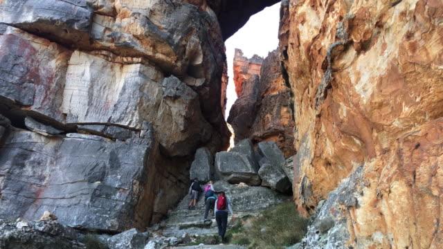 stockvideo's en b-roll-footage met familie die omhoog naderende rotsen in een woestijncanyon klimt - vrij klimmen