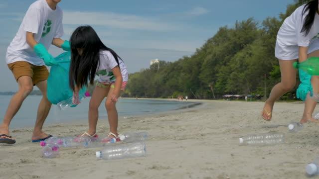 vídeos de stock e filmes b-roll de family collecting litter on beach in the vacation. - apanhar atividade física