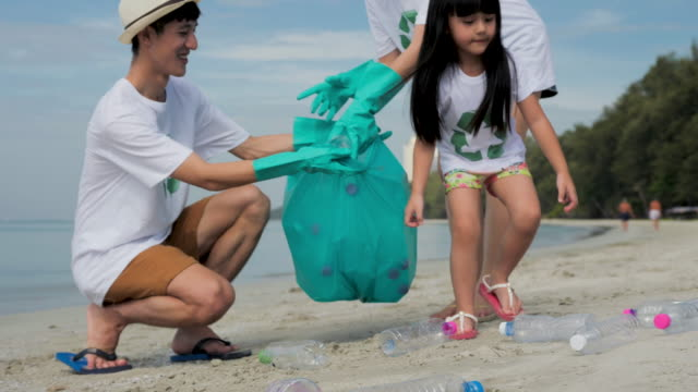 family collecting litter on beach in the vacation. - lift stock videos & royalty-free footage