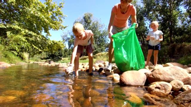 familie sammelt recycling aus dem fluss und lernt nachhaltigkeit - umweltschutz reinigungsaktion stock-videos und b-roll-filmmaterial