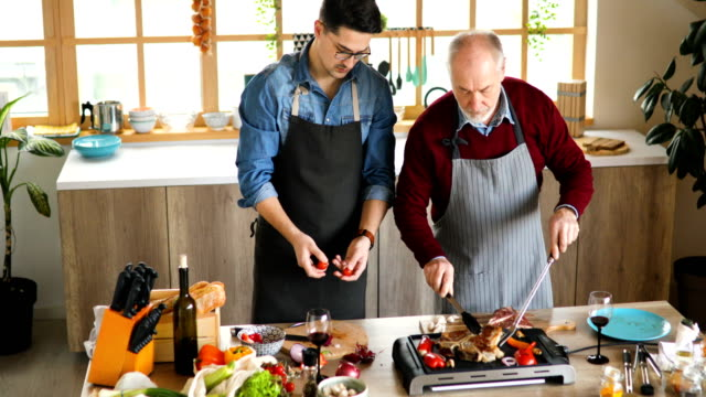 vídeos y material grabado en eventos de stock de clases de cocina familiar. padre e hijo cocinando en cocina - adulto