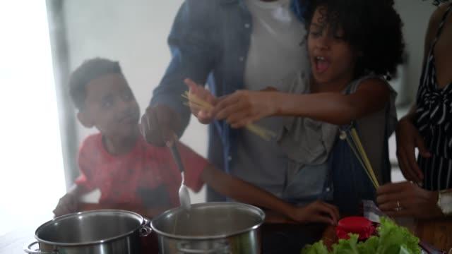 vídeos de stock, filmes e b-roll de família que cozinha junto na cozinha - preparing food