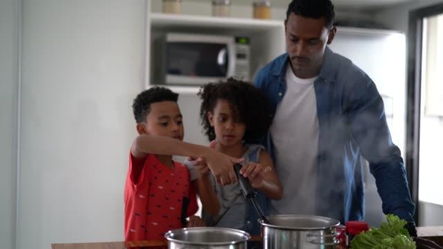 vídeos de stock e filmes b-roll de family cooking together at kitchen - pai solteiro