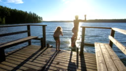 Family couple with daughter running on a wooden pier and jumping into the lake