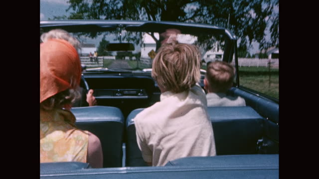 ms family - couple with two children -  enjoying road trip in convertible car, children bouncing on seat with no seatbelts / united states - family convertible stock videos & royalty-free footage