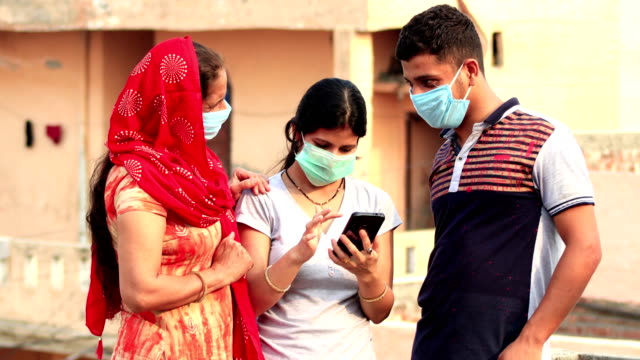 family covering  face with pollution mask for protection from viruses and the all using mobile phone together at home - india stock videos & royalty-free footage