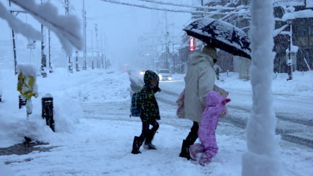 family cross snow covered road during major winter snow storm in northern japan - major road video stock e b–roll