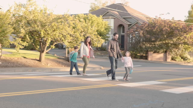 family crossing the street on a sunny evening - quarter stock videos & royalty-free footage