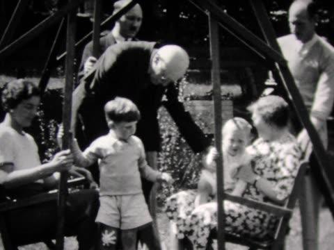 vidéos et rushes de 1931 family crowds into large swing - 1931