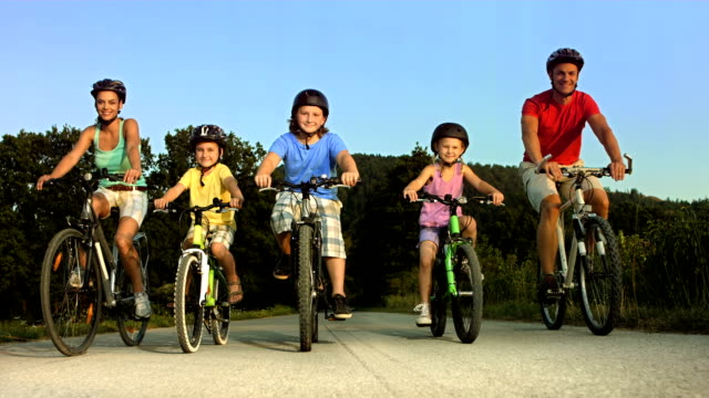 hd: family cycling at dusk - family with three children stock videos & royalty-free footage