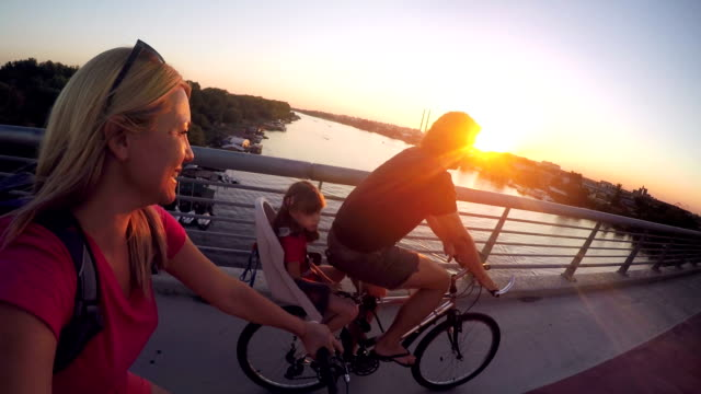 family cycling in the city together at sunset - bicycle seat stock videos & royalty-free footage