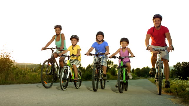 hd: family cycling in the late afternoon hours - family with three children stock videos & royalty-free footage