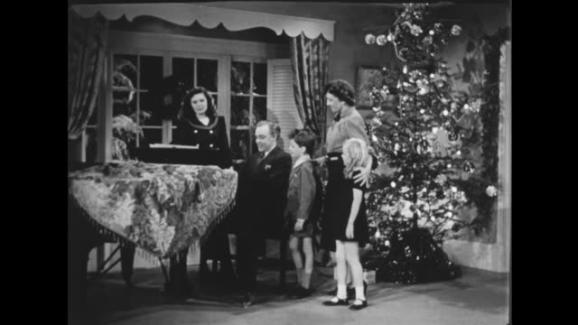 1941 family decorates christmas tree and enjoys being together on christmas eve - stockings stock videos & royalty-free footage