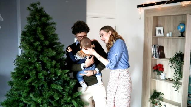 vídeos de stock, filmes e b-roll de família de decorar a árvore de natal - enfeitar a árvore de natal