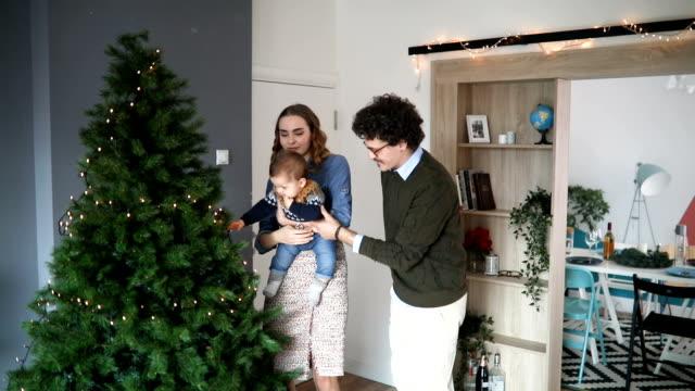 vídeos de stock e filmes b-roll de family decorating christmas tree - enfeitar a árvore de natal