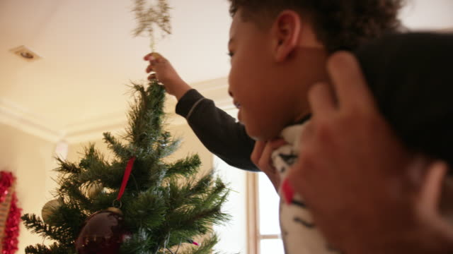 family decorating christmas tree - christmas tree stock videos & royalty-free footage