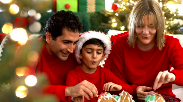family decorating gingerbread house on christmas - decorating stock videos & royalty-free footage