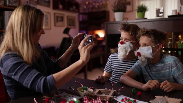 famiglia decora maschere chirurgiche per il natale - photographing video stock e b–roll