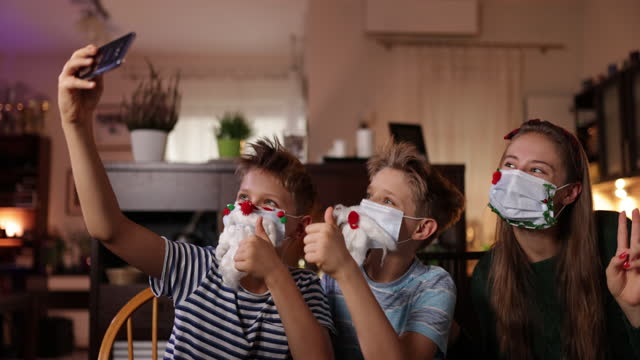 family decorating surgical face masks for christmas - christmas stock videos & royalty-free footage