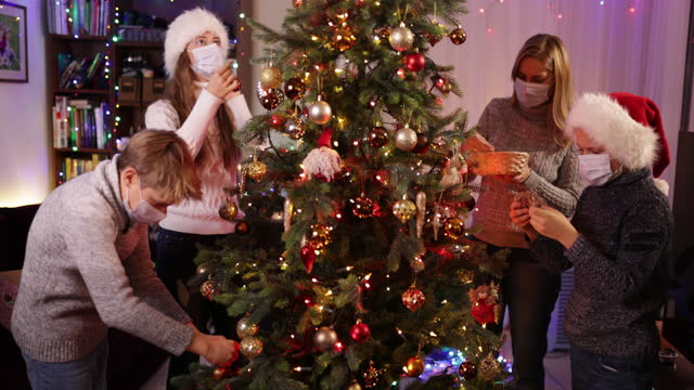 family decorating the christmas tree during the covid-19 pandemic - decorating stock videos & royalty-free footage