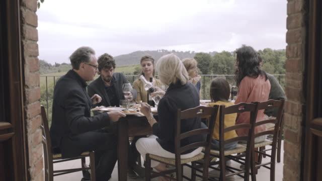 vídeos de stock, filmes e b-roll de family dining outdoors - varanda