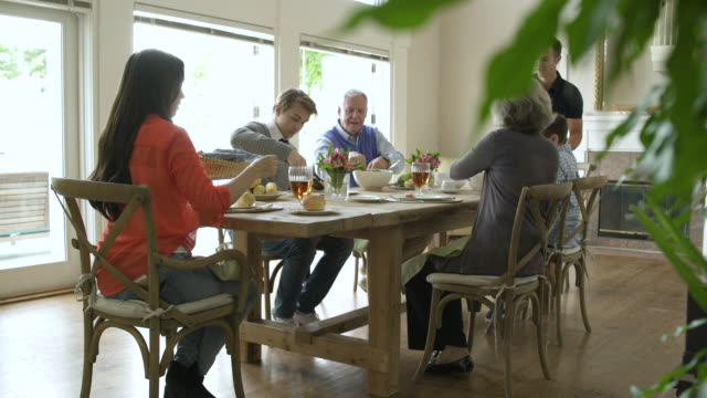 family dining together at dining table. - image focus technique stock videos & royalty-free footage