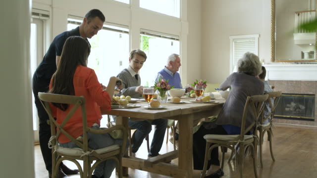 vidéos et rushes de family dining together at dining table. - famille multi générations