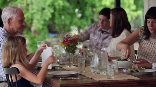 ms family dishing up dinner at table outdoors on front porch of home - serving size stock videos & royalty-free footage