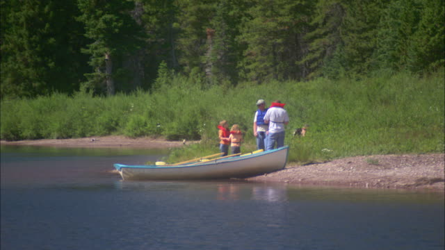 A family docks their rowboat on a lake shore in Glacier National Park, Montana.