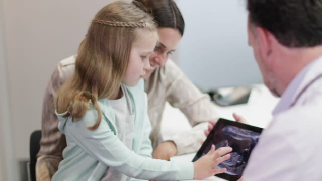 family doctor showing mother and daughter a baby ultrasound - fetus stock videos and b-roll footage