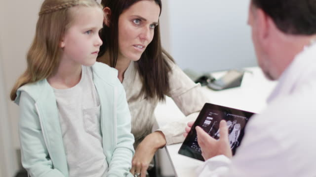 family doctor showing mother and daughter test results - daughter stock videos and b-roll footage
