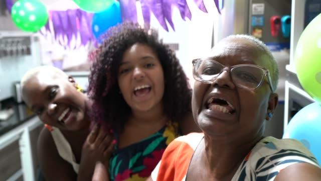 Famille faisant un appel vidéo à la partie de distance d'anniversaire - POV de la caméra