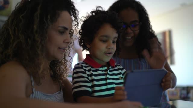 vídeos de stock, filmes e b-roll de família fazendo uma chamada de vídeo usando tablet digital em casa - família de dois filhos