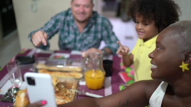 vídeos de stock, filmes e b-roll de família fazendo um bate-papo de vídeo no celular no café da manhã em casa - imagem em movimento