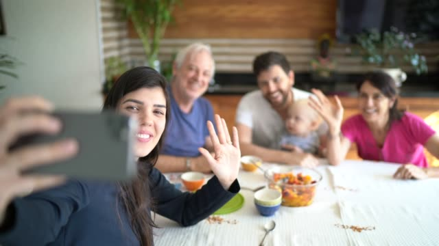 family doing a video chat with mobile phone at home - social gathering stock videos & royalty-free footage