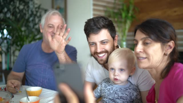family doing a video chat with mobile phone at home - greeting stock videos & royalty-free footage