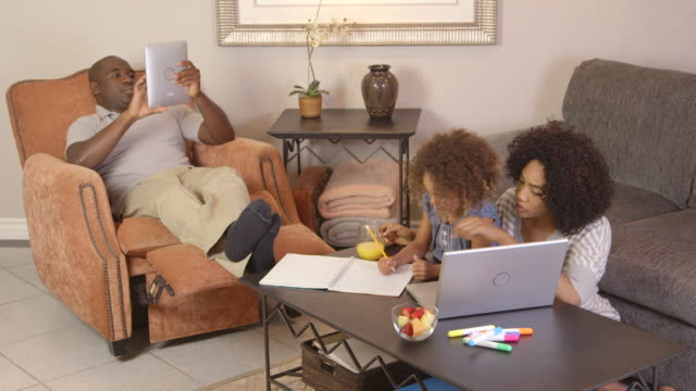 family doing homework with laptop