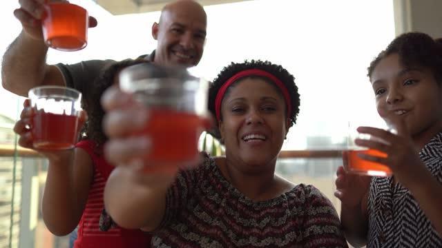 vídeos de stock, filmes e b-roll de família fazendo videodesque e fazendo um brinde comemorativo em casa - ponto de vista da webcam - distante