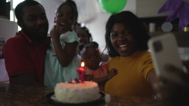 Familj gör videosamtal - ringer någon på födelsedagsfest hemma