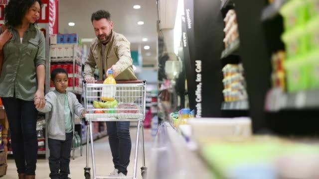 vídeos y material grabado en eventos de stock de family doing weekly shop in grocery store - 6 7 años