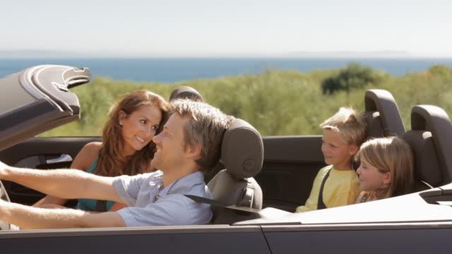 vídeos de stock e filmes b-roll de family driving in convertible car - convertible